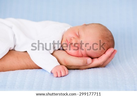 Newborn baby sleeping in arms of his father. Dad holding new born son. Child taking a nap on parent hand. Infant kid sleeping on a blue blanket. Textile bedding for kids. Parents and children bonding.