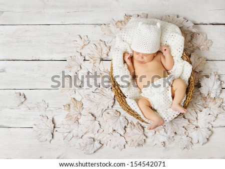 Newborn baby sleeping in basket on leaves over white wooden background. - stock photo