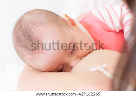 Newborn baby sleeping in mother breast. Adorable infant kid. Child and mom closeness.