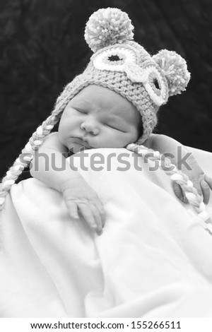 Newborn baby sleeping in the blanket wearing a hat - stock photo