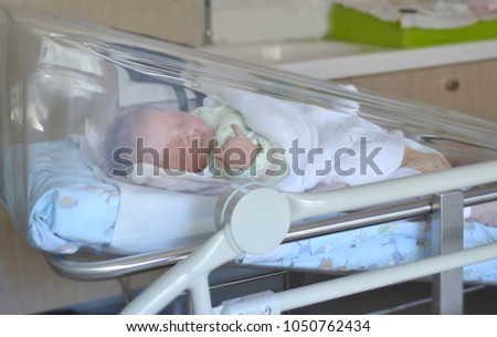 Newborn Baby Sleeping In The Hospital Bed