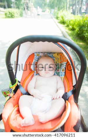 Newborn baby sleeping in white stroller on a walk in summer park. New born child napping outdoors on hot sunny day. Infant in a city buggy. Kids sleep in pram. Close up portrait of cute little boy. - stock photo