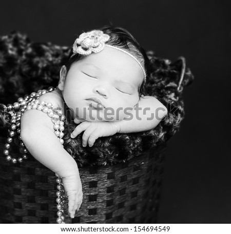 Newborn baby  sleeping inside a basket, resting on arms and elbows, on background. Wearing pearls and flower headband. Black and white. - stock photo