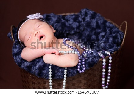 Newborn baby  sleeping inside a brown basket, resting on arms and elbows, on brown background. Wearing purple pearls and flower headband. - stock photo