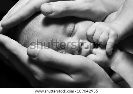 Newborn baby sleeping into parents hands. Concept: kids protection by parents. Closeup. Monochrome. - stock photo