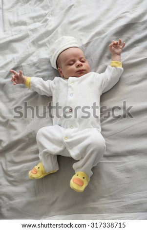 Newborn baby sleeping on a bed at home