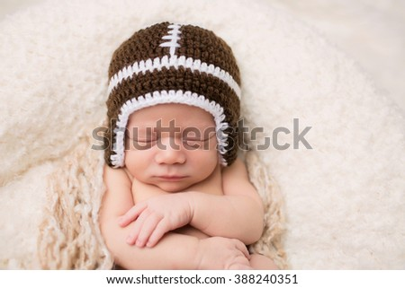 Newborn Baby sleeping on a blanket, wearing a knit football hat
