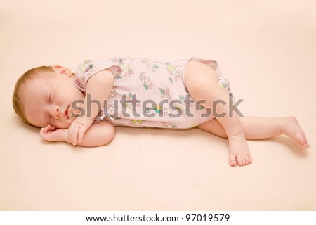 Newborn baby sleeping on a blanket with his hands under his cheek. Isolated on a beige background with clipping path - stock photo