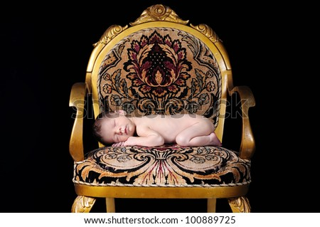 Newborn baby sleeping on an antique chair - stock photo
