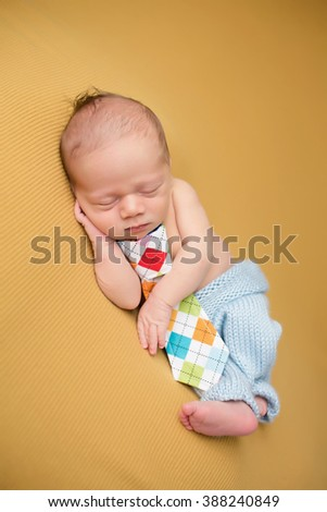Newborn baby sleeping on blanket, asleep, posed, in knit outfit with a tie, parenting concept. - stock photo