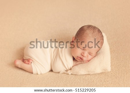 Newborn baby sleeping on blanket on his tummy