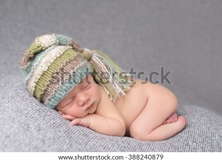 Newborn baby sleeping on blanket on his tummy, asleep in a knit hat, posed - stock photo