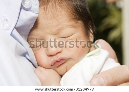 Newborn baby sleeping on dad - stock photo