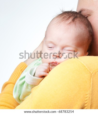 Newborn baby sleeping on father's hands. Beautiful little baby in father's hands feeling so comfortable and in great protection. People posing in studio over white background. - stock photo