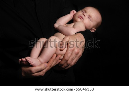 newborn baby sleeping on hands of the father on the black background - stock photo