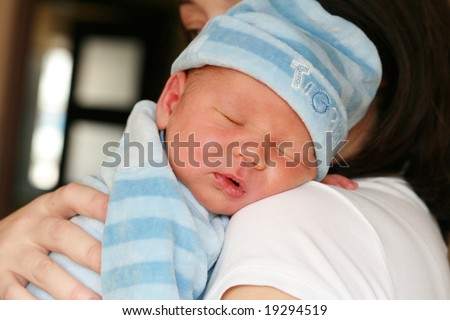 Newborn baby sleeping on her mothers arms. - stock photo