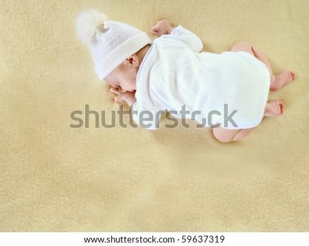 Newborn baby sleeping on her tummy on soft yellow blanket - stock photo