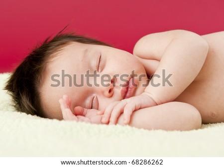 Newborn baby sleeping on its side - stock photo