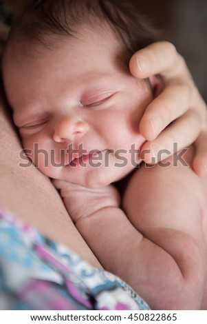 newborn baby sleeping on mother and smiling - stock photo