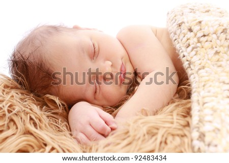 Newborn baby sleeping on soft fur under a knit blanket - stock photo