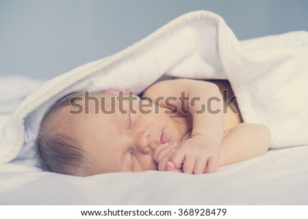 newborn baby sleeping sweetly . The first tender days of an infant's life