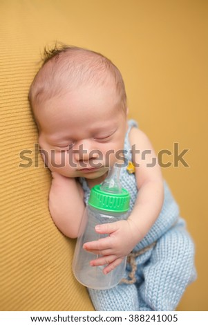 Newborn baby sleeping with a bottle, in blue knit outfit, on blanket. Bottle feeding concept.