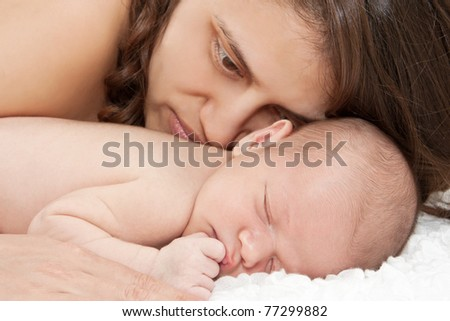 Newborn baby sleeping with mother - stock photo