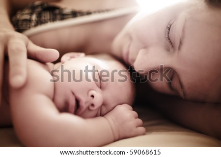 Newborn baby sleeping with mother. Shallow DOF. - stock photo
