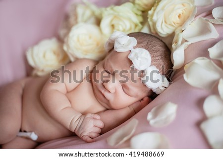 newborn baby sleeps in a flower wreath on the head among rose petals