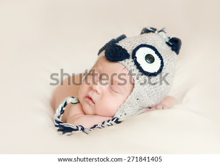 newborn baby sleeps in a hat owl - stock photo