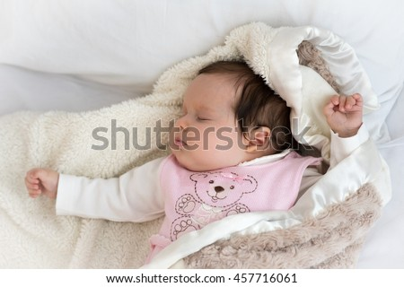 Newborn baby sleeps on the bed in woolen clothes