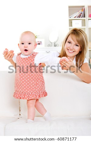 Newborn baby start walking with help of happy mother - At home - stock photo