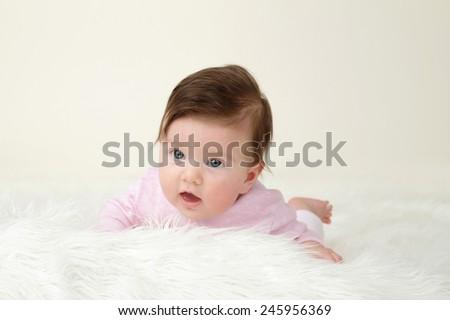 Newborn Baby tummy time on white soft fur, blank copyspace - stock photo