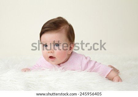 Newborn Baby tummy time on white soft fur, blank copyspace - stock photo