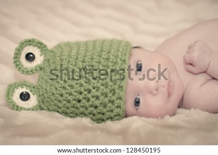 Newborn baby wearing a frog crochet hat and looking at the camera