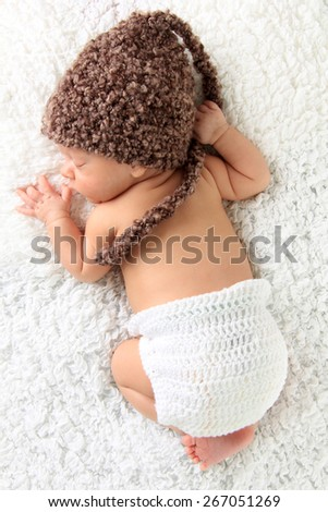Newborn baby wearing a knitted hat and knitted diaper cover.  - stock photo