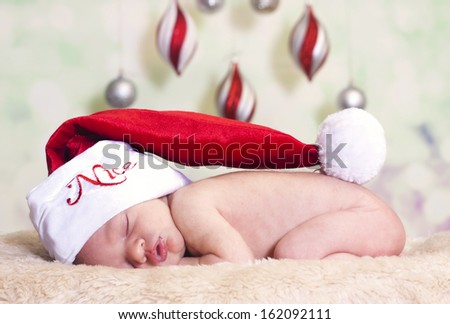 newborn baby wearing a Santa hat and sound asleep.