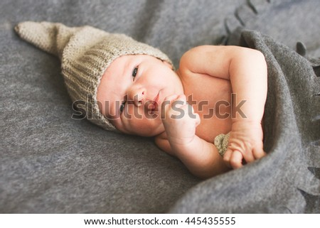 newborn baby  with a toy lying next to the  knitted teddy bear - stock photo