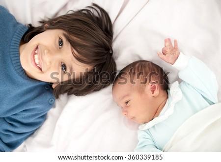 Newborn baby with bigger brother - stock photo