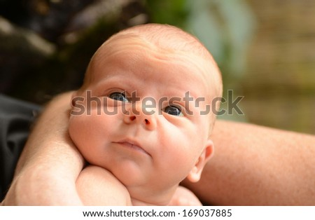 newborn baby with bright eyes held by mother - stock photo