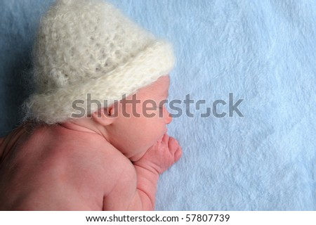 Newborn baby with cap is sleeping on blue blanket. - stock photo