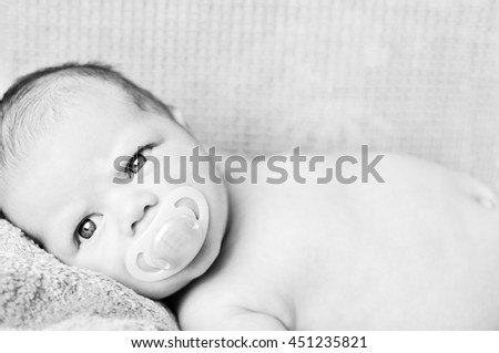 newborn baby with dummy on the bed
