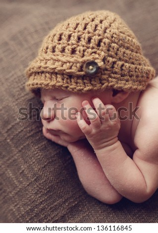 Newborn baby with hands on his face - stock photo