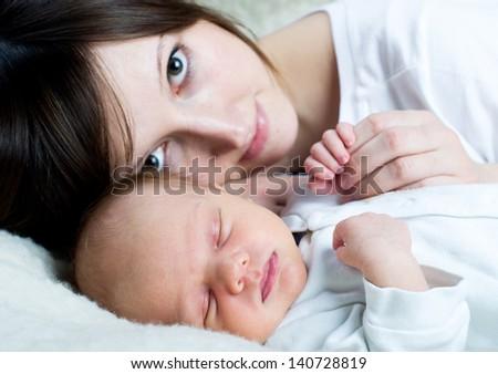 Newborn baby with happy mother - stock photo