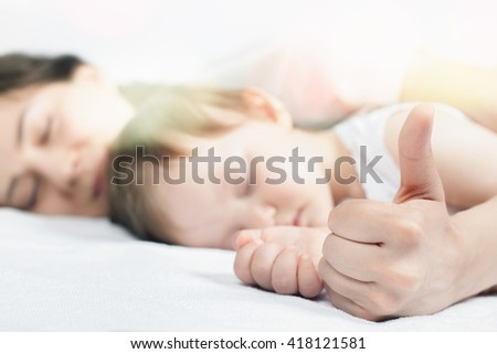 Newborn baby with mother sweet sleeping and holding hands on a white bed. Comfortable bed. Concept of baby care. Care concept. Healthy sleep. Healthcare - stock photo