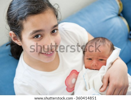 Newborn baby with sister - stock photo