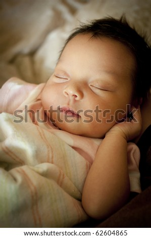 Newborn baby wrapped in blanket sleeping on her back. - stock photo