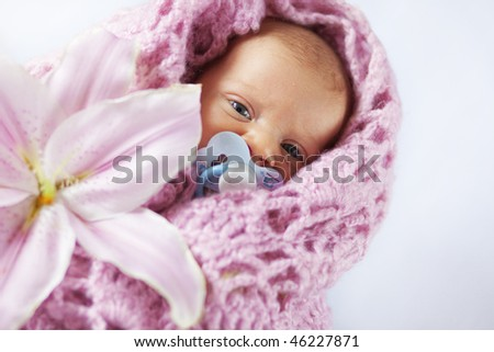 Newborn baby wrapped in knitted cover - stock photo