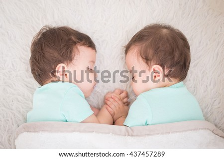 Newborn beautiful baby twins sleeping with pacifier. Closeup portrait, caucasian child - stock photo