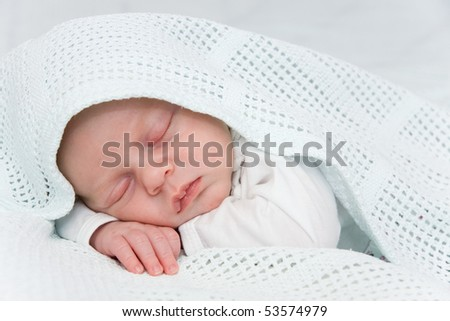 Newborn boy covered by blue blanket sleeping - stock photo